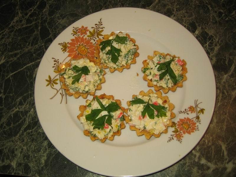 Готовые корзиночки наполнить приготовленным салатом, украсить зеленью петрушки; теперь крабовые тарталетки можно подать к столу