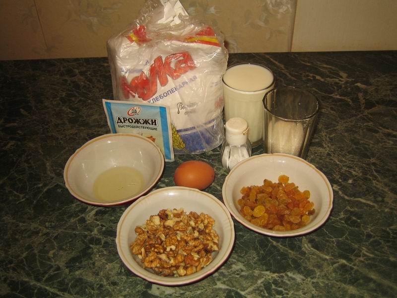 Список продуктов: мука - 4 стакана, молоко - 1 стакан, растительное масло - 2 столовые ложки, сахар - 1 столовая ложка, яйцо - 1 шт., сухие быстродействующие дрожжи - 10 гр., грецкие орехи - 100 гр., изюм - 100 гр., сливочное масло и соль - по вкусу