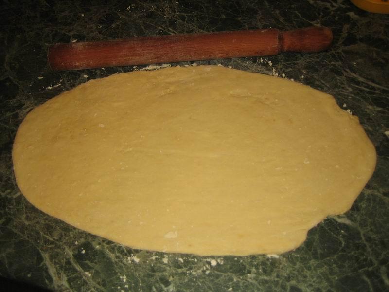 Когда тесто поднимется, его нужно раскатать на столе, посыпанном мукой, в лепёшку овальной формы (толщиной примерно 0,5 см)
