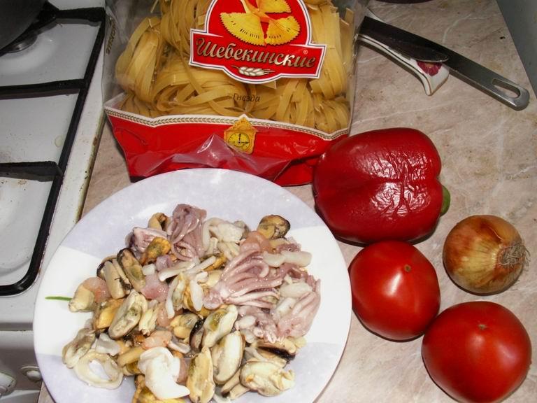Список продуктов: макароны - 450 гр., мороженые морепродукты (мидии, креветки, кольца кальмаров, щупальца осьминога и т.д.) - 300 гр., луковица - 1 шт., помидоры - 2 шт., красный перец - 1 шт., растительное масло - 3-4 столовые ложки, соль - по вкусу